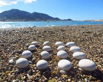 16 small round white pebbles polished by Mediterranean Sea HD picture on the beach.