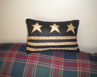 Accent pillow measuring 7x11 in black with coffee dyed stars and stripes