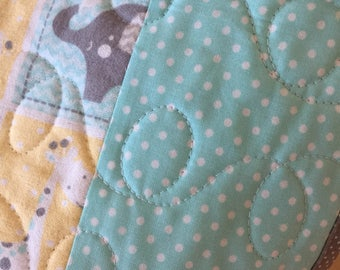 Patch work elephant print in cotton flannel.the backing is a aqua,,white flannel,and Machine quilted by me. An heirloom quality quilt.