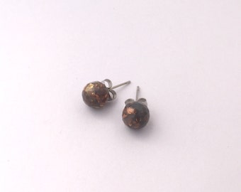 Polished concrete grey eco-resin studs with embedded gold and copper on allergy-friendly backs.