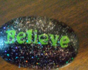 Believe on black river rock with sparkles