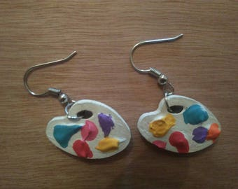 Earrings dangle in the shape of painter's palette