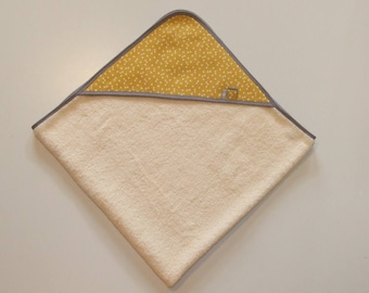 Bath sponge printed white triangles on a background mustard yellow and gray