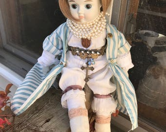 HAPPYLAND porcelain shoulder doll. Blinged out with vintage collectable jewelry.rhinestone brooches.Brass cross.Goldfilled pins.glass pearls