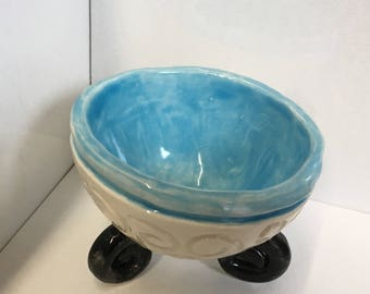 Pinch Pot with coiled feet and a carved design that match the coiled feet.