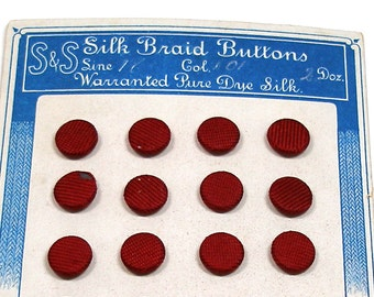 "1900s Silk BUTTONS, 24 Antique maroon silk braid, unused on original card, 7/16""."