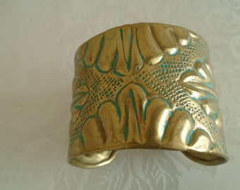 brass cuff with raised pattern and simulated verdigris colouration