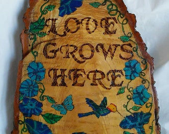 Love Grows Here garden art wood burned and painted tree trunk slice wedge with a hummingbird, blue flowers and green vines and leaves.