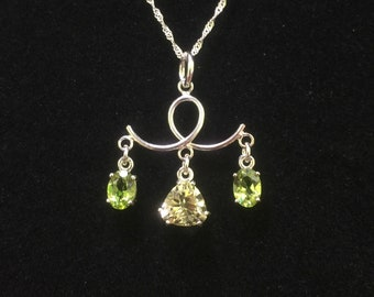 Citrine trillion and peridot oval gemstones upon sterling loop.