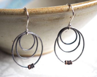 Graduated wire oval earrings with heishi beads.