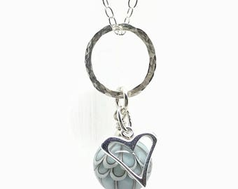 """Turquoise blue charm necklace with sterling silver heart and glass lampwork bead. Hung on an 18"""" sterling silver trace chain."""