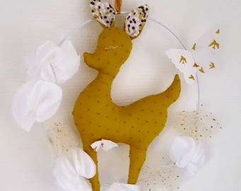 Golden deer mobile with wreath of white flowers