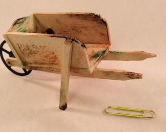 Miniature antique wooden wheelbarrow with metal wheel. 1:12 inch dollhouse scale. Handmade USA.