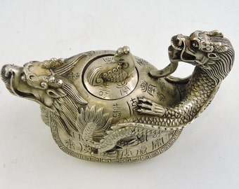 A white metal teapot in the form of a tortoise, with a dragon head spout and handle
