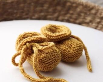 Handknitted pure wool baby booties in mustard.