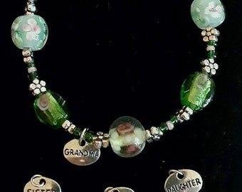 Bracelet made with lamp work beads and personalized charm.Mother's Day,green,flowers,charm,pink,spring,pretty,unique,one of a kind,gift