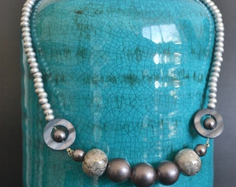 Silver-coloured wooden beads necklace with an intermediate piece of gemarmerdkeramiek, laminated wood, glass pearls and shells between pieces
