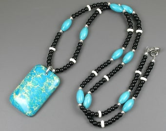 Turquoise magnesite pendant on beaded strand of turquoise blue magnesite, obsidian, bone, and silver plated beads