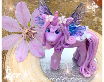 A sculpted polymer clay unicorn with wings.
