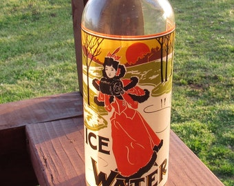 """Ice Water Glass Bottle with ceramic stopper and wire bail, ice skating, Winter scene, 1980's, 12 1/2"""" tall"""