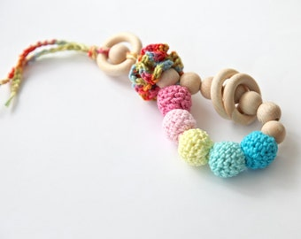 Teething toy rattle with crochet wooden beads and 3 wooden rings. Yellow, pink, aqua blue/ cyan.