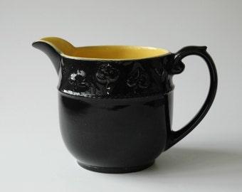 Vintage dark brown pitcher with yellow interior