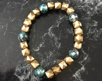 Handmade beaded bracelet in gold with turquoise accents.