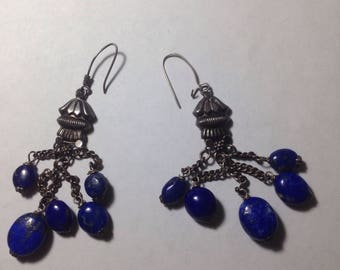 Silver earings with blue rocks dangling.