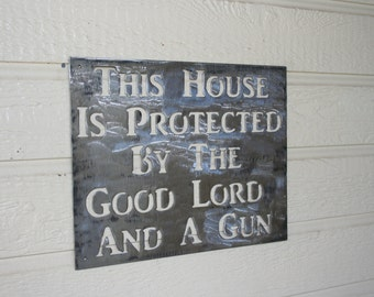 This House is Protected by Good Lord and a Gun Metal sign