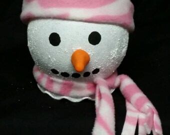 This is a cute, adorable light up snow person with a pink and white zebra print scarf and hat.