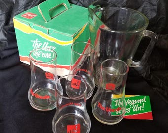 7 Up Uncola glasses in the original box and a 2 quart pitcher 4 glasses and an advertising paper