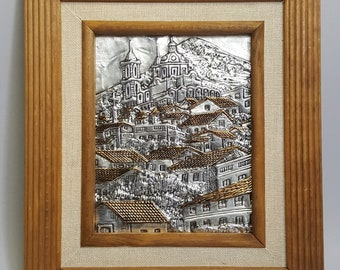 A vintage two-tone embossed hammered metallic artwork hilltop scenery with village church view.