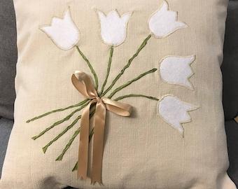 White felt tulip bouquet, green ribbon stems, beige decorative ribbon, on beige background