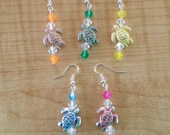A silver/painted Turtle is the focal point of these earrings. It is contrasted with Swarovski bicone beads