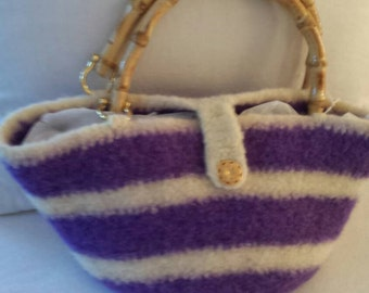 A crocheted felted purse with a bamboo handle.