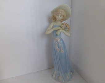 "Porcelain Girl Figurine, ""Gathering Flowers"", House of LLoyd,  1998 Blue Dress Pink Ribbon Belt Holding Flower Bouquet"