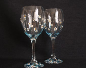 Pair of hand painted wine glasses decorated with daisies in a summery gold, white and blue design. Would make a lovely gift.