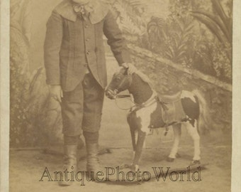 Cute boy with toy horse antique cabinet photo