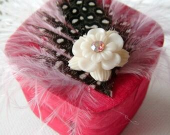 petite boîte carrée bois peint en fuchsia, plumes mauve et noir/blanc,fleur en plastique écru, centre en strass rose