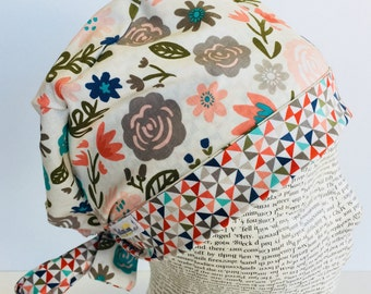 Tie Back Scrub Cap scrub hat featuring a beige material with flowers in peach teal and green with a coordinating band 2t