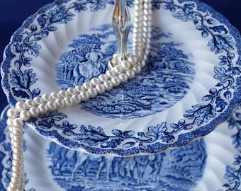 A vintage Myotts 'Country Life' two tier cake stand in fabulous blue and white, depicting English country scenes on each plate. c1960s.