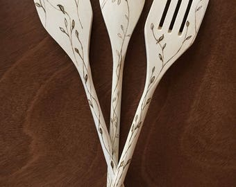 Woodburned wooden slotted spatula with vines and leaves