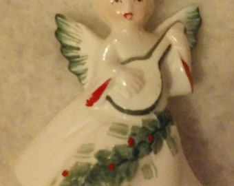 A Vintage Ceramic Angel Playing A Mandolin