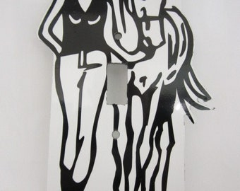 Light switch cover plate with cowgirl and horse design.