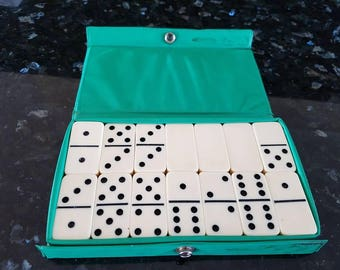 A vintage dominoes game with plastic tiles in a plastic case