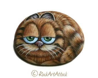 The Garfield Cartoon Cat Hand Painted Pebble! Painted with high quality Acrylic paints and finished with Glossy varnish.