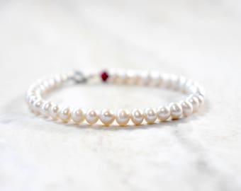 freshwater pearl beaded bracelet with garnet detail. dainty beaded pearl bracelet. creamy white pearls. fresh water pearl jewelry