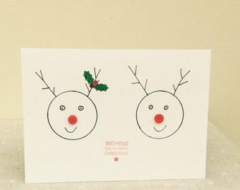 Fun Christmas reindeer. Red  button nosed reindeer. Foil holly sparkle on antler. Seasonal card.Happy Christmas card. Jolly reindeer card.