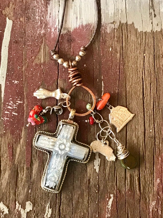 el coche.   Carved Mother of Pearl cross pendant and assorted milagros and beads gathered onto a copper bale. On leather cord.
