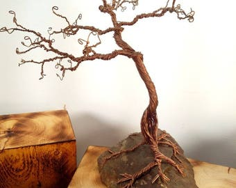 hand twisted narled copper tree with a hole in the trunk sitting atop a New Hampshire stone.